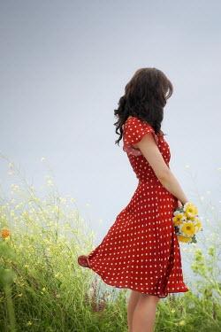 ILINA SIMEONOVA GIRL IN SPOTTED DRESS HOLDING FLOWERS IN FIELD Women