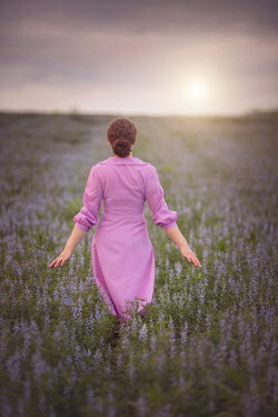 Joanna Czogala Woman walking through lavender field Women