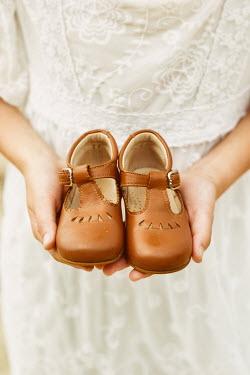 Krasimira Petrova Shishkova Girl holding child's shoes Children
