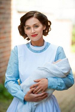 Lee Avison pretty 1940s nurse holding a baby