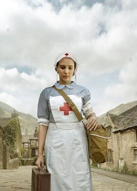 Stephen Mulcahey A wartime nurse  walking through a village Women