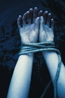 Magdalena Russocka close up of woman's hands tied with rope in dark water