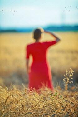 Ildiko Neer Red dress woman standing at wheat field