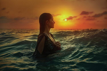 Terrence Drysdale WOMAN STANDING IN SEA AT SUNSET Women