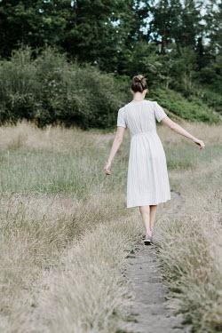 Jacinta Bernard Young woman in striped dress walking on track