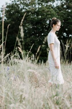 Jacinta Bernard Young woman in striped dress walking in field