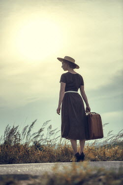 Magdalena Russocka silhouette of retro woman with suitcase standing on country road at sunset