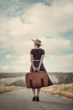 Magdalena Russocka retro woman with suitcase standing on country road