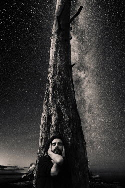Daniil Kontorovich Man by leaning on tree covering his ears under stars