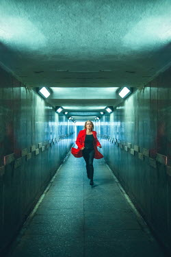 Joanna Czogala Scared young woman running in tunnel