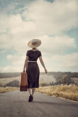 Magdalena Russocka retro woman with suitcase walking on country road