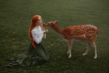 Nathalie Seiferth Young woman petting deer in field