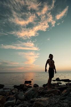 Daniil Kontorovich SILHOUETTED MAN ON ROCKS BY SEA Men