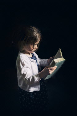 Evelina Kremsdorf Little girl reading in darkness Children
