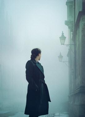 Mark Owen Woman in foggy street by buildings Women