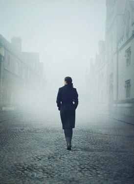 Mark Owen Woman walking through foggy street Women