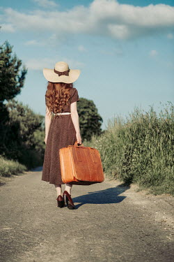 Magdalena Russocka vintage woman with suitcase in countryside Women