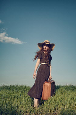 Magdalena Russocka young woman with suitcase standing in field Women