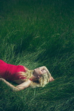 Joanna Czogala BLONDE WOMAN IN RED SLEEPING IN FIELD Women