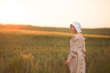 Joanna Czogala MEDIEVAL WOMAN IN BONNET OUTDOORS AT SUNSET Women