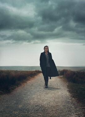 Mark Owen Woman walking through country path Women