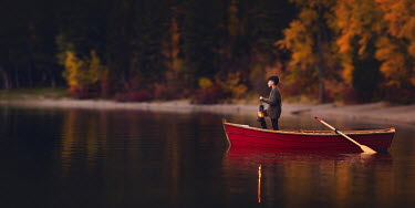 Lisa Holloway Boy with lantern in red rowboat on lake