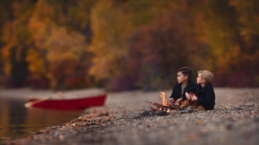 Lisa Holloway Boys sitting by campfire on lakeshore