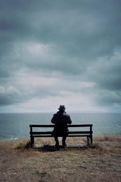 Tim Robinson MAN IN HAT ON BENCH WATCHING SEA Men