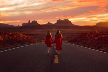 Lisa Holloway TWO GIRLS HOLDING HANDS IN DESERT AT SUNSET Women