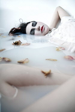 Virginia Ateh WOMAN LYING IN MILKY WATER WITH PETALS Women