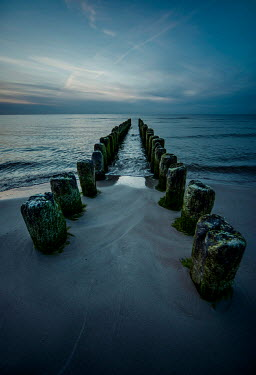 Jaroslaw Blaminsky WEATHERED POSTS IN SEA AT DUSK Seascapes/Beaches