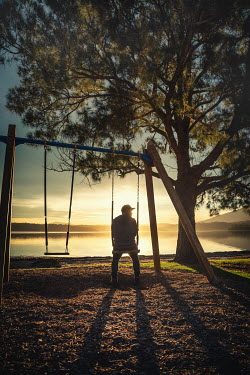 Evelina Kremsdorf MAN SITTING ON SWING BY SUNLIT LAKE Men