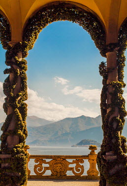 Nikaa ARCHWAY WITH PLANTS BY LAKE WITH MOUNTAINS Lakes/Rivers