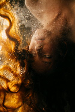 Marta Syrko WOMAN WITH RED HAIR LYING BEHIND WET GLASS Women