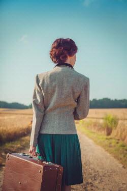 Joanna Czogala Retro woman with suitcase in field Women