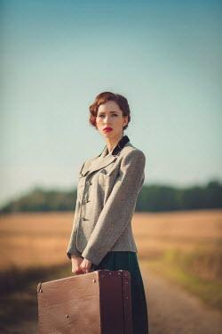 Joanna Czogala Retro woman stood in country field Women