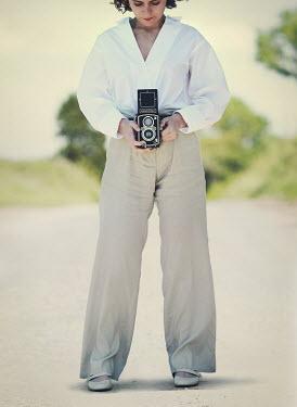 Mark Owen Woman taking photographs on retro camera Women