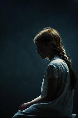 Magdalena Russocka sad little girl sitting in dark room Women