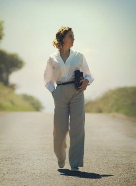 Mark Owen retro woman carrying camera in road Women