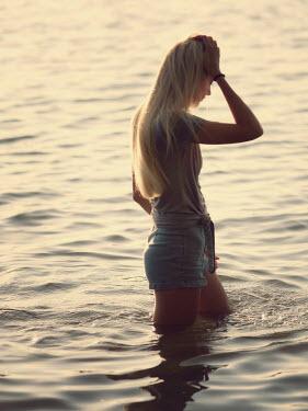 Elisabeth Ansley BLONDE GIRL STANDING IN SUNLIT WATER Women