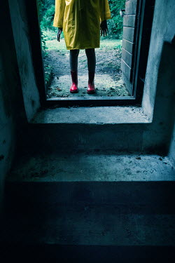 Magdalena Russocka child wearing yellow raincoat entering basement