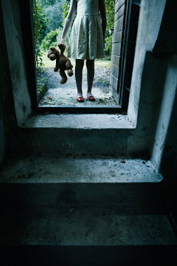 Magdalena Russocka little girl with teddy bear entering basement