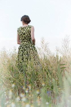 Helen Mayer WOMAN IN PATTERNED DRESS IN FIELD FROM BELOW Women