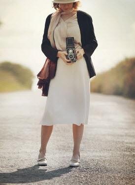 Mark Owen Woman holding retro camera in road Women