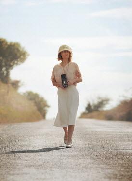 Mark Owen Woman walking with retro camera Women