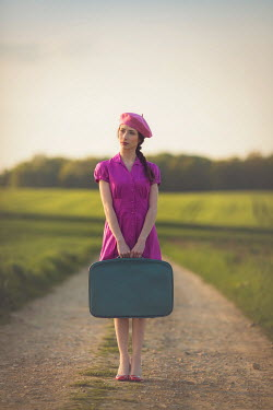 Joanna Czogala Retro woman holding suitcase in countryside Women
