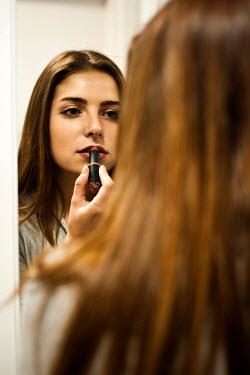 Jitka Saniova Girl applying lipstick in mirror Women