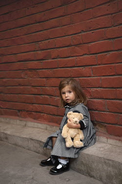Kerstin Marinov LITTLE GIRL HUGGING TEDDY SITTING IN STREET Children