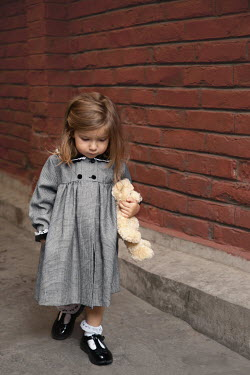 Kerstin Marinov LITTLE GIRL WALKING WITH TEDDY IN STREET Children