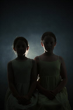 Magdalena Russocka two little girls sitting in dark room